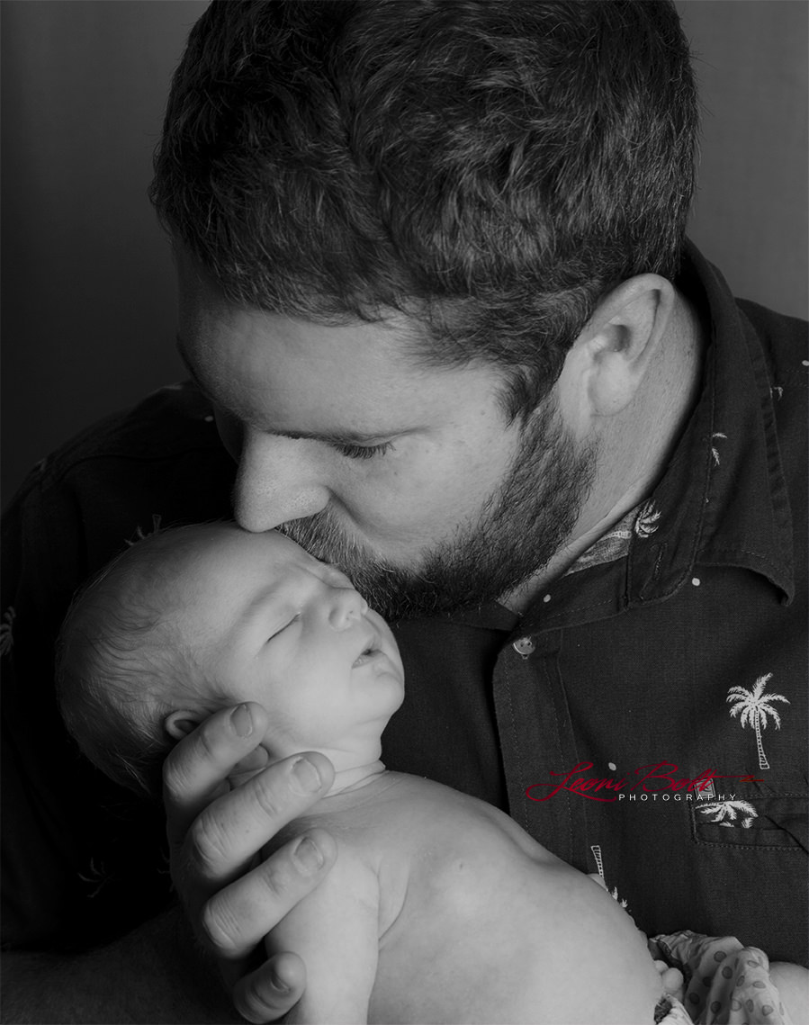 dad kissing newborn